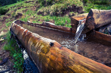 trough: A source in the mountains in a wooden trough. Stock Photo