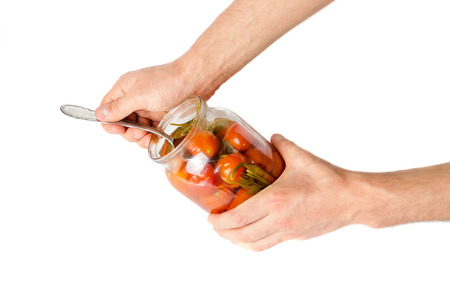 Masculine hands draw out tomatoes a spoon from a glass jar . Stock Photo