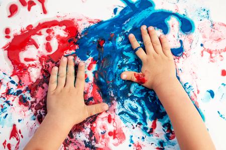 Manos pintadas manchando colores en papel desordenado.