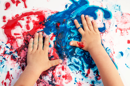 Painted hands smudging colors on messy paper . 版權商用圖片 - 103156639