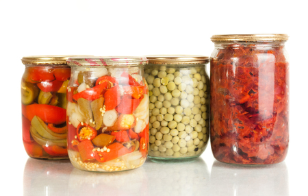 collection set of canned vegetables in glass jars isolated on white background .