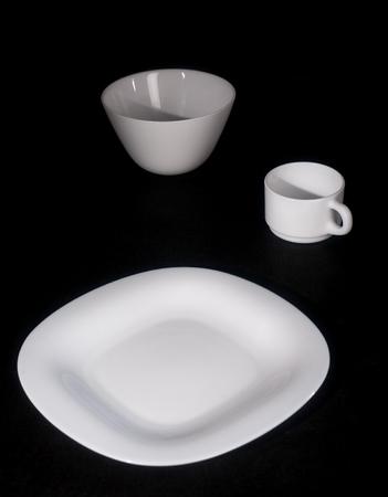 White plate with a mug on a black background .