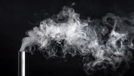 Smoke from a pipe on a black background . Stock Photo