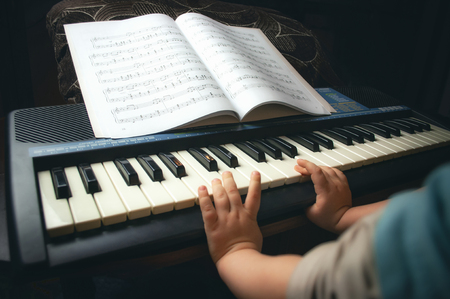 Childrens hands learn to play the piano . 写真素材