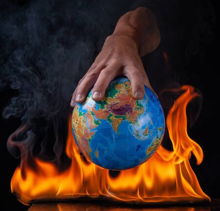 The hand holds the planet Earth in the fire . Stock Photo
