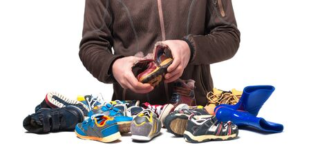 Hands are sorting out shoes and clothes from second hand .