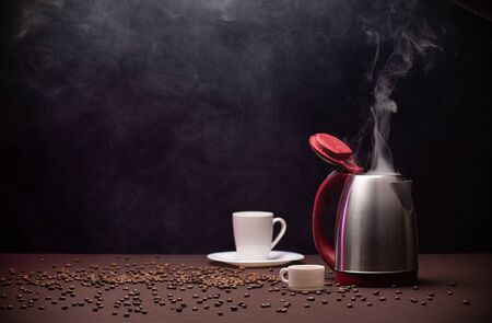 Electric kettle and coffee beans on dark background .