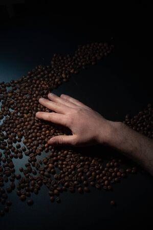 Workers hands holding coffee beans in the dark Standard-Bild