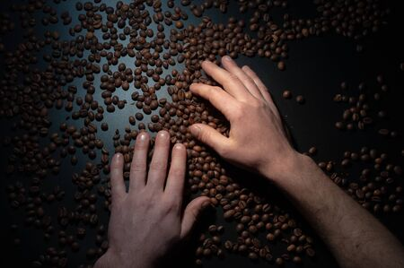 Workers hands holding coffee beans in the dark .