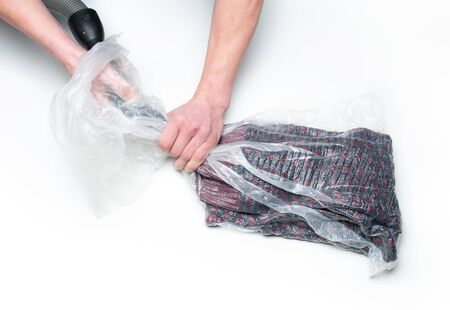 Man packs clothes into a vacuum bag