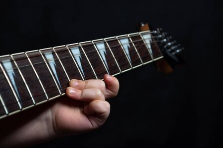 Children's hand close up learning guitar playing .