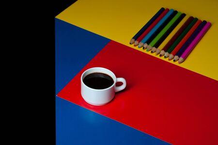 White mug on red paper. Black background .