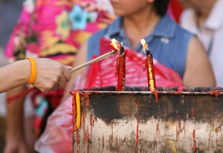 Burning incense and candles in a temple to bring good luck at Chinese New Year photo
