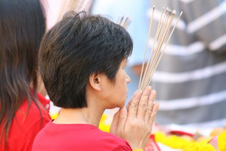 Praying and burning incense at a temple for Chinese New Year photo