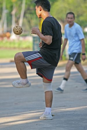 tradional: A game of circle takraw using a rattan ball. Players stand in a circle and try to keep the ball airborne as long as possible. The game is popular in Thailand, Malaysia and the Phillipines Stock Photo