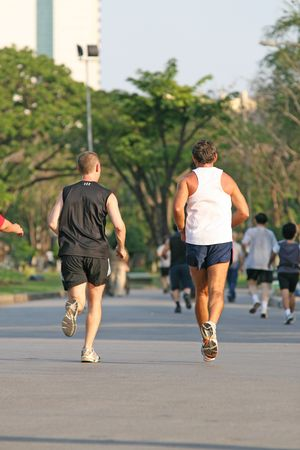 Two men running together in a park popular for jogging Stock Photo