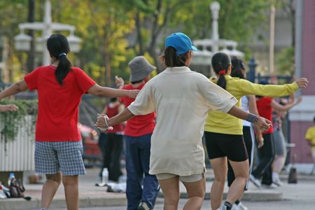 supple: A group of people join in with a workout as part of an aerobics class in the park