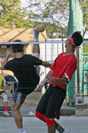 tradional: Player makes a high overhead kick in Sepak Takraw (Kick Volleyball). The game is a cross between soccer and volleyball and is popular in Thailand, Malaysia and Indonesia.  Stock Photo