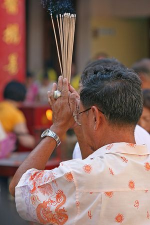 Praying and burning incense in a Chinese temple photo