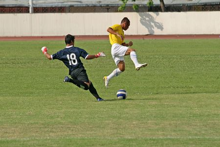 Player makes a blocking tackle as the footballer shoots