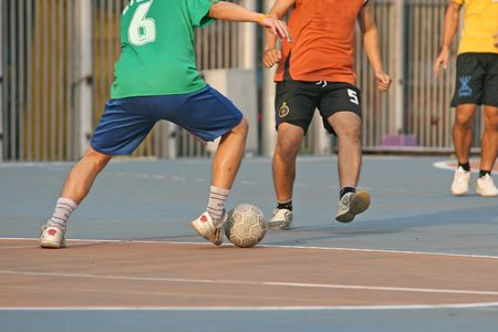 footwork: Player make a tackle in a game of street football (soccer)