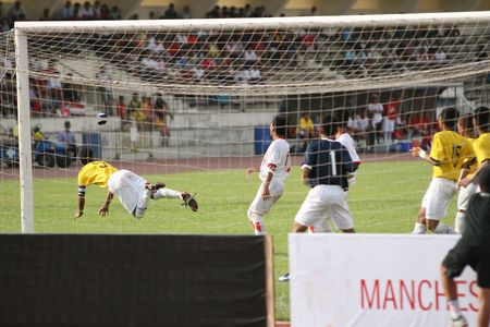 Football (soccer) player makes a headed clearance