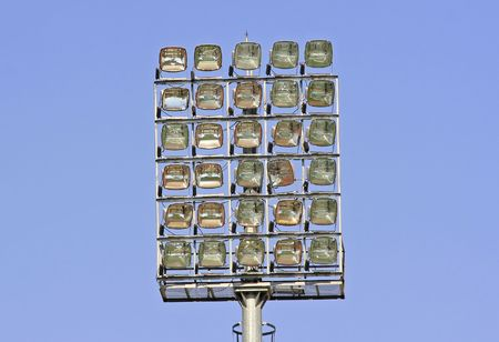 outdoor lighting: Rows of stadium lights against a blue sky
