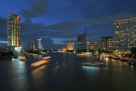 Streaking lights of boats on the Chao Praya River in Bangkok, at dusk Stock Photo