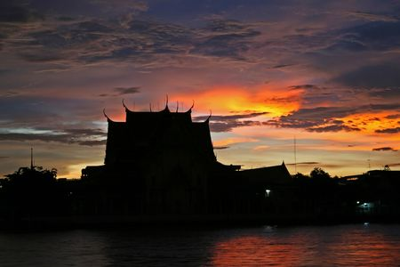 chao praya: A storm just before sunset produces a dramatic sky over a temple on the Chao Praya River in Bangkok Stock Photo