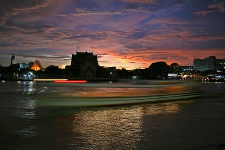 chao praya: A boat leaves streaking lights on the Chao Praya River in Bangkok, shortly after a storm at sunset produces a dramatic sky
