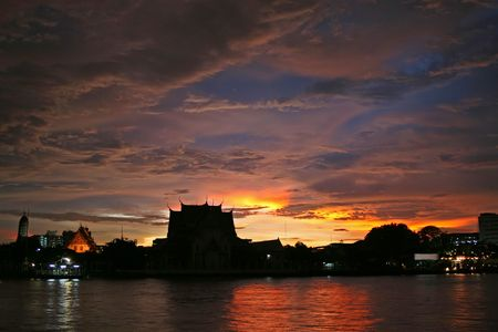 praya: Sky ablaze with color over a temple on the Chao Praya River in Bangkok at sunset