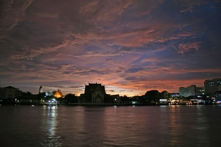 chao praya: A scenic view of the Chao Praya River in Bangkok, with a temple in the background. A storm shortly before sunset produces a colourful and dramatic sky