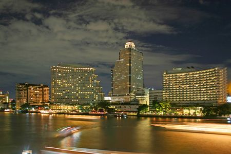 chao: Night falls over the Chao Praya River in Bangkok, with boats leaving streaking lights
