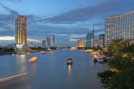 trailing: Boats on the Chao Praya River in Bangkok at dusk Stock Photo