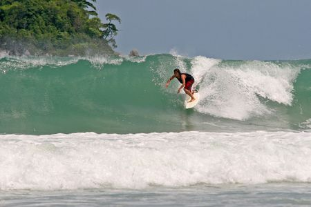 Surfer tucks into a clean tropical wave photo