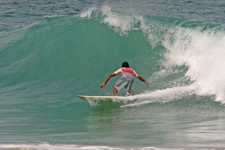 short wave: Surfer performs a bottom turn on a peeling tropical wave Stock Photo