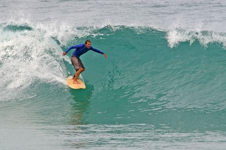 A shortboard surfer rides a clean tropical wave