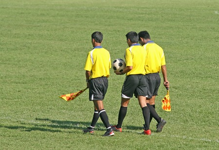 footwork: Referee and linesmen walk out for a game of football Stock Photo