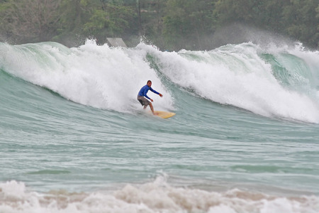 that: A surfer catches a huge wave that rolls into a beach in Phuket, Thailand