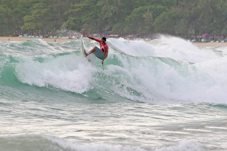 A local surfer hits the lip of a wave on a beach in Phuket, Thailand photo