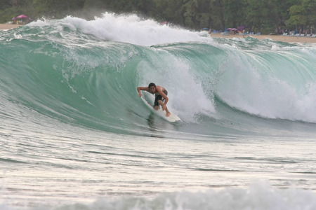 A surfer tucks into a hollow wave and attempts to get barrelled photo