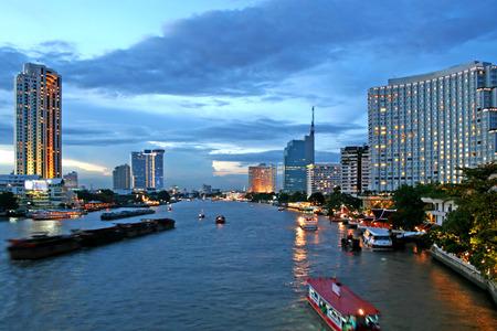 Boats make their way along the Chao Phraya River at dusk Stock Photo