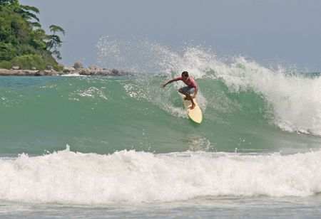 short wave: A local surfer tucks into a hollow wave on a beach in Phuket, Thailand