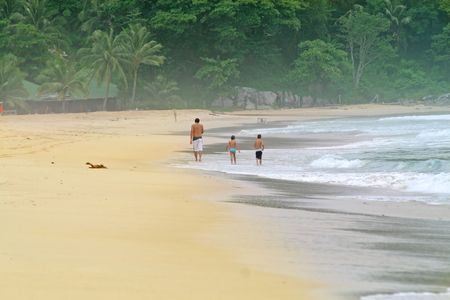 Tourist walking along a tropical beach in Thailand. Rainforest in the background photo