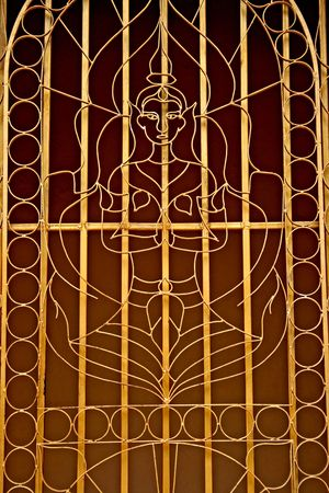 window grill: Window grill made from metal featuring an elaborate Buddhist design Stock Photo