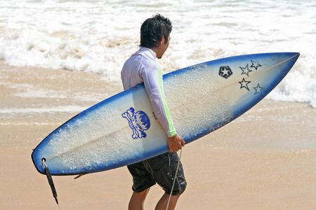 Close up of a surfer carrying his board