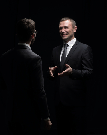 geste: Close up photo two businessmen in suits discussing isolated in b