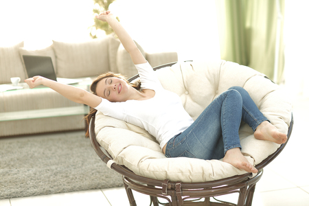 keeping room: Beautiful young woman keeping eyes closed while sitting on comfo