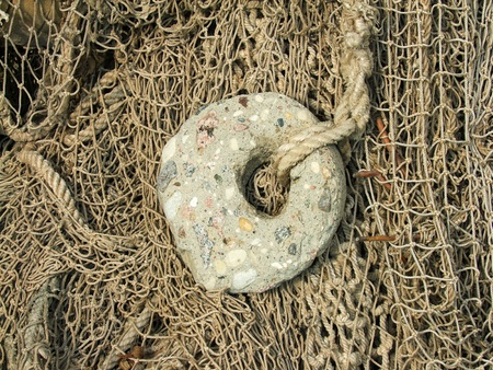 toils: stone sinker and old fishing nets closeup