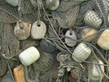 toils: float, stone sinker old fishing nets catch closeup